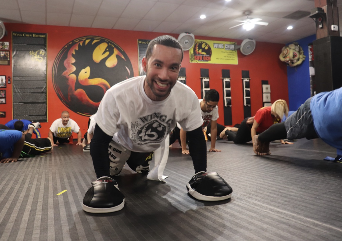 wing chun fitness student smiling at camera while in push up position on exercise mat